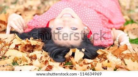 Horizontal image of a cheerful girl with blue eyes lying in autumn leaves