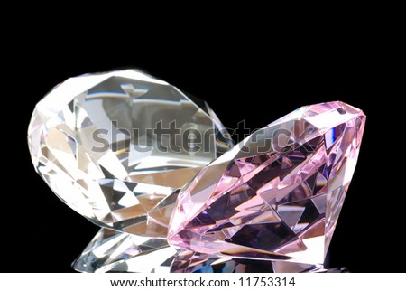 Horizontal Image of a Colored and a Clear Diamond Cut Gems Against a Black Background