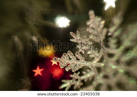 Horizontal image of a plastic snow-flake ornament taken with a selective focus (lens-baby) lens, with star shaped bokeh.