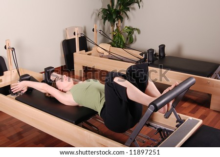 Horizontal image of a professional Pilates instructor excercising on a Reformer. - stock photo