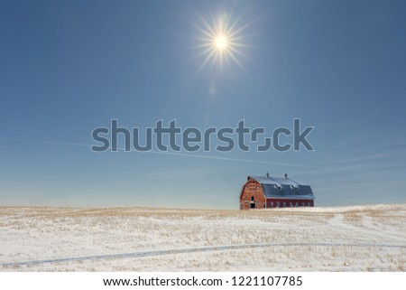 horizontal image of a red barn sitting in the distance on a snow covered field with a star burst sun shining through a blue hazy sky.