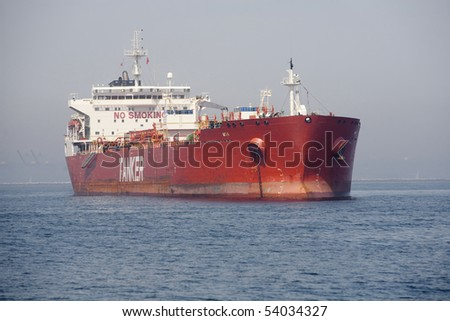 "Horizontal image of a red Ultra Large Crude Carrier, or ""Super Tanker.""  These vessels are capable of carrying up to two million barrels of oil across the seas."