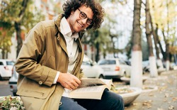 Horizontal image of a young man reading a book outdoors. College male student learns on campus in the autumn street. Smiling smart guy with curly hair wears spectacles and reading books in the city.
