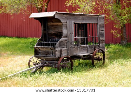 Horizontal image of an antique jail wagon against a red barn, standing beneath trees and in tall grass.