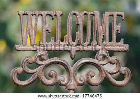 Horizontal image of an iron sign spelling out the word Welcome.
