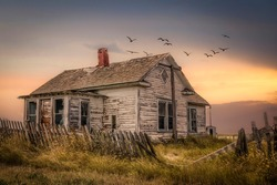 horizontal image of an old abandoned farm house with a broken wooden picket fence under a beautiful early evening sky with the sun setting and birds flying overhead in the fall.