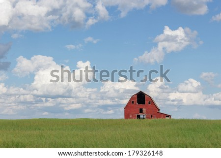 horizontal image of an old abandoned red barn sitting in a field of green grass under a blue sky filled with white clouds in the summer time.