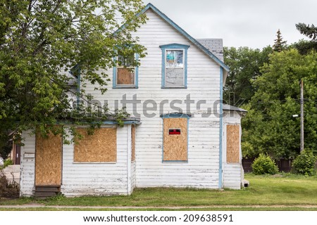 """Photo of  horizontal image of an old condemned house with windows boarded up and """"no trespassing sign"""" with big tree in front in summer time"""