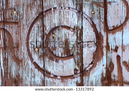 Horizontal image of an old, weathered and worn barn door with a number of brands marring it.  The copyright symbol is featured in this image.