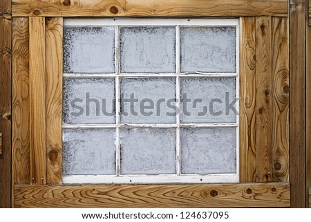 Horizontal image of an old wooden nine-lite window pane in a wooden wall, covered in ice crystals. - stock photo