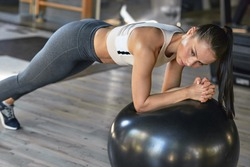Horizontal image of athlete woman doing exercises with fit ball at the gym. Caucasian gumnastic girl doing core exercises with an medicine ball in a sport club woman training pilates in the modern gym
