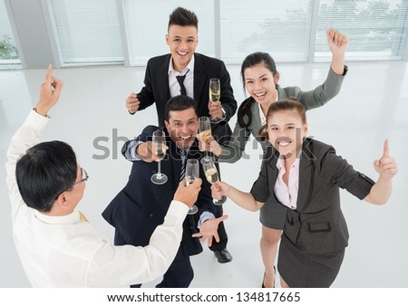 Horizontal image of cheerful businesspeople raised their hands with champagne