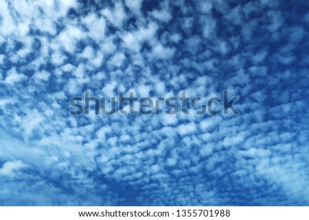 Horizontal image of Cirrocumulus or Altocumulus clouds in exotic blue sky in tropical summer morning sunlight. Nature background of beautiful puffy & fluffy white cloud spreading & cover navy blue sky
