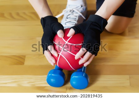 Horizontal image of female hands wearing workout gloves while lifting red weight ball of off blue dumbbells on wooden gym floor