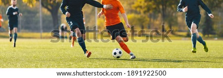 Photo of  Horizontal image of football players running in a duel on a tournament match. Soccer forward player compete with defender. Anonymous football players kicking league game
