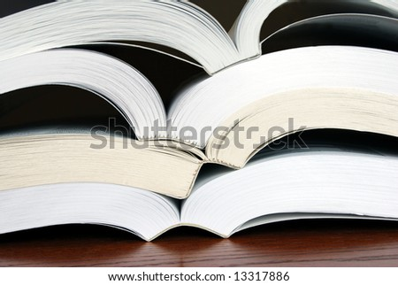 Horizontal image of four open books stacked upon each other so their spines more or less nest into the next book.