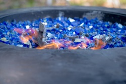 horizontal image of gas fire pit with flames in vibrant cobalt blue fire glass