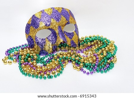 Horizontal image of green, gold and purple mardis gras beads and a purple and gold harlequin mask covered with glitter to commemorate the February celebration that is a huge holiday in New Orleans.