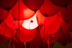 Horizontal image of red ballons with strings with one ballon lit white. Could represent red and white blood cells