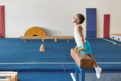 Horizontal image of skilled Afro American boy gymnast preparing for artistic gymnastics competition, exercising on pomme horse. performing difficult routine. Balance, strength and determination