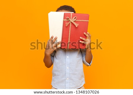 Horizontal image of unrecognizable dark skinned little boy wearing shirt covering face with white and red box with birthday gift, candies or sweets inside, posing at blank yellow studio wall