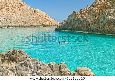 horizontal image of young caucasian couple swimming in turquoise crystal clear waters of Seitan Limania secluded beach on sunny summer day, Crete, Greece