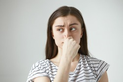 Horizontal isolated studio shot of frustrated frowning young dark haired woman having disgusted look, pinching her nose and holding breath because of unpleasant disgusting smell, odor or stink