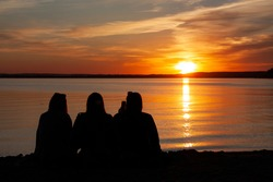 Horizontal landscape conceptual photo with a silhouettes of three female friends with their backs to the camera, sitting on a seashore and relaxing during beautiful sunset at calm evening