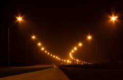 Horizontal landscape low angle view photo of an empty highway at night illuminated with warm orange lite by road lamps standing along both sides of the highway