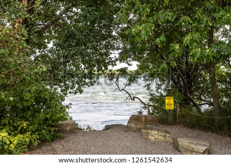 Horizontal landscape of a small dirt path, flanked by rocks, trees and foliage that leads to the rapids at Rapids Park in Lasalle, Quebec