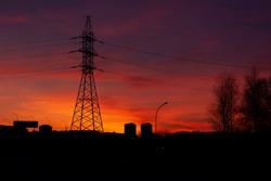 Horizontal landscape photo with a silhouette of a single steel tower of high voltage electric power line support against colorful sky at dawn after sunset