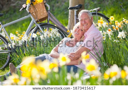 Horizontal low angle shot of a seated senior couple cuddling over a blanket by a daffodil field on a sunny day with their bicycles parked in the background smile at the camera.