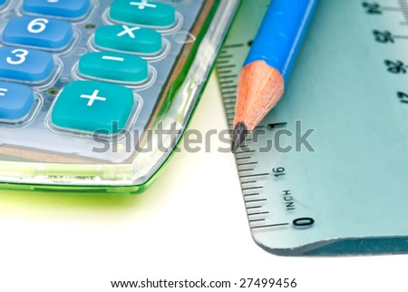 Horizontal macro of a blue pencil with a calculator and ruler