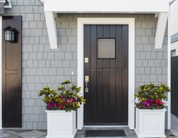 Horizontal of black front door to a family home; The door is vertical wood boards, with a window, framed by two planters, gray shingles, and a door mat. Also seen is a porch light fixture.