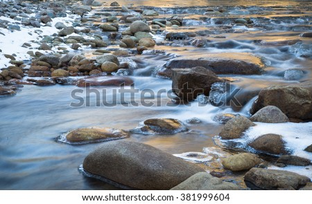 horizontal orientation color image, taken with slow shutter speed, to show water flowing over rocks with ice formations, in winter / Winter Scenery and Flowing Water