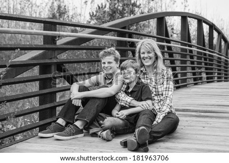 horizontal orientation of a beautiful woman sitting with her two sons outside on a bridge in black and white with copy space / Making Time for Each Other