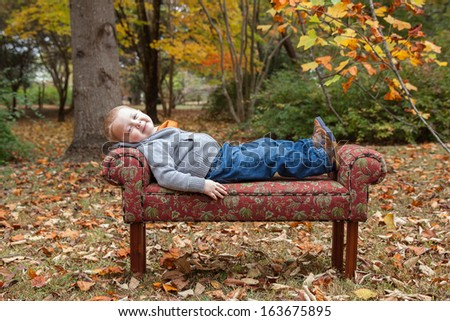 horizontal orientation of a happy toddler boy on a couch in the middle of a park with fall colors /  Trouble Sleeping? - stock photo