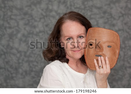 horizontal orientation of a single woman with a slight smile holding a clay mask in one hand with neutral  grey background and copy space / Masking the Symptoms of Mental Illness