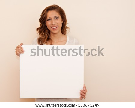 horizontal orientation of happy smiling teenage girl holding a blank, white, sign with copy space and neutral background / Pleased to Meet You!