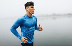 Horizontal outdoor image of young runner man running in the morning on the fog lake background. Fitness male exercising in the park and listenting the music on earphones. People and sport concept