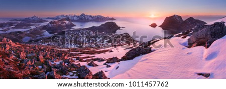 Horizontal panoramic photo of an aerial winter sunset taken at Norwegian Lofoten. Surrounding mountains, peaks, hills and islnads are clearly visible. #1011457762