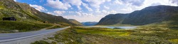 Horizontal panoramic view of winding road along mountains and lake. Breathtaking mountain landscape of the Norwegian nature. Ultimate road trip destination to Scandinavia. Green moss clouds blue sky.