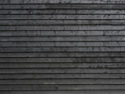 horizontal part of black painted wooden planks of barn wall or shed