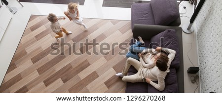 Horizontal photo above view couple resting sitting on couch, small kids play run in living room at new home, relocation and buy house concept, banner for website header design with copy space for text