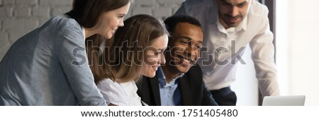 Horizontal photo banner for website header design, diverse employees gathered in office having fun watching funny video, discussing new ideas, brainstorming using laptop enjoy break in workday concept