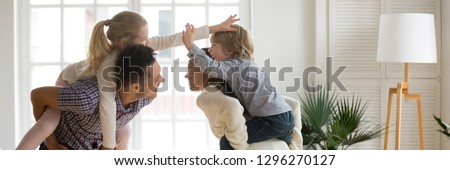 Horizontal photo cheerful parents laughing piggybacking little kids play in living room at home family having fun enjoy time together concept, banner for website header design with copy space for text