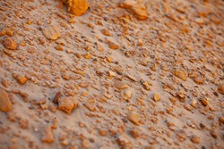horizontal photo. dark orange brown sand. many small stones and fragments of shells on a mountain of sand. summer time. sunny day. sand quarry.