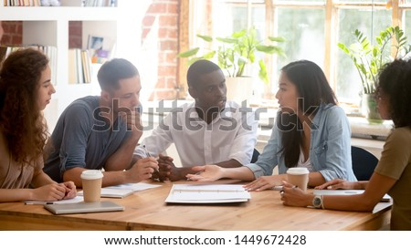 Horizontal photo diverse employees team discussing project at meeting, colleagues listening to Asian businesswoman, colleagues sitting at office table, students study together in classroom or library