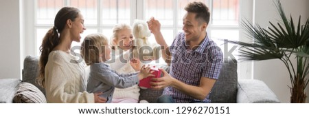 Horizontal photo happy family little kids sitting on sofa celebrating father day presenting gift box make surprise congratulate birthday, life events holidays concept, banner for website header design