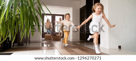 Horizontal photo happy little kids running into new home, parents with cardboard boxes on background. Loan mortgage, moving relocating concept banner for website header design with copy space for text